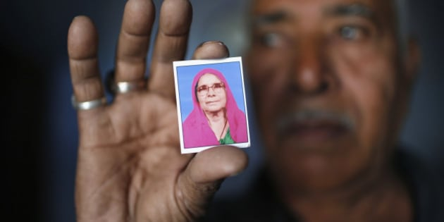 Kasam Bhai Mansoori, a Muslim, displays a photograph of his mother Sona Ben Mansoori at his house which was burnt and damaged in the Gujarat 2002 riots at the Gulbarg Society, a Muslim-dominated housing, in the western Indian city of Ahmedabad February 28, 2014. Narendra Modi's critics depict him as an autocratic Hindu supremacist who would tyrannize the country's minority Muslims if his Bharatiya Janata Party (BJP) came to power. Modi himself insists he is a moderate who will create a prosperous India for people of all creeds.  Picture taken February 28, 2014. To match Special Report INDIA-MUSLIMS/ REUTERS/Ahmad Masood (INDIA