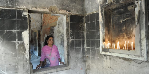 Suraiya Ankleshwaria looks on as she and others pay homage to those killed at Gulbarg Society following the February 2002 Godhra train incident, which sparked communal riots that year, on the ninth anniversary of the incident in Ahmedabad on February 28, 2011. A total of 69 people were killed in the Gulberg Society carnage, including former Congress Member of Parliament Ehsan Jafri on February 28, 2002. The aftermath of the Godhra Train carnage resulted in widespread communal riots across Gujarat where more than 2,000 were killed. A Special Court has reserved the pronouncement of quantum of punishment to the 31 convicted in the Godhra Train Carnage incident till March 1. AFP PHOTO / Sam PANTHAKY (Photo credit should read SAM PANTHAKY/AFP/Getty Images)