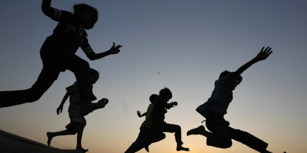 Children play on a sand dune as they are silhouetted against the setting sun in the western Indian city of Ahmedabad November 28, 2014. REUTERS/Amit Dave (INDIA - Tags: SOCIETY TPX IMAGES OF THE DAY)