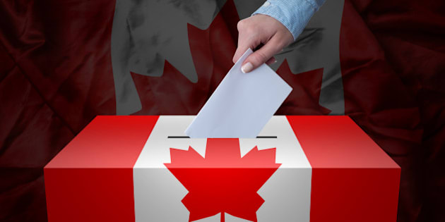 A hand casting a vote in a ballot box for an election in the Canada