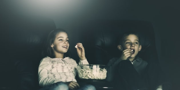 boy and girl, eating popcorn, watching a movie in their home theater