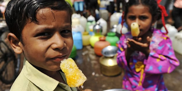Indian children enjoy ice lollies as they wait for their mothers to fill containers with drinking water in Mumbai on World Water Day March 22, 2010. The UN has kept clean water for a healthy world as its theme  this year. Demand for clean water has become critical for developing countries like India, where untreated wastewater, industrial growth and rising population make clean water a rare commodity. Mumbai city has been reeling under a water shortage since June last year, when levels at the six lakes that supply water daily to the city, started running low. Last year India suffered its worst monsoon rains since 1972, which triggered a water problem. Mumbai needs four billion litres (1.1 billion US gallons) of drinking water a day to meet the needs of its estimated 18 million residents but can currently only supply 3.3 billion litres (872 million US gallons).  AFP PHOTO/ Sajjad HUSSAIN (Photo credit should read SAJJAD HUSSAIN/AFP/Getty Images)