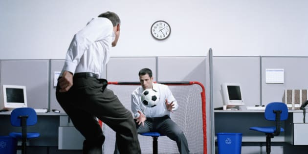 Two businessmen playing soccer in office, goalie catching ball