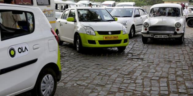 In this March 29, 2016 photo, Ola cabs, left, waiting for customers are parked next to other cars in Kolkata, India. Aiming to wrest control of India's booming taxi market, two cab-hailing smartphone apps, Uber and Ola, are promising hundreds of millions in new investments while also facing off with one another in court. (AP Photo/ Bikas Das)