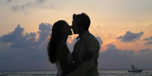 Couple kissing on their wedding day on Isla Mujeres, Mexico.