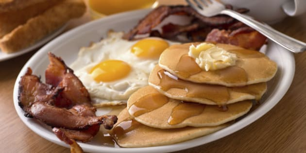 A delicous home style breakfast with crispy bacon, eggs, pancakes, toast, coffee, and orange juice.