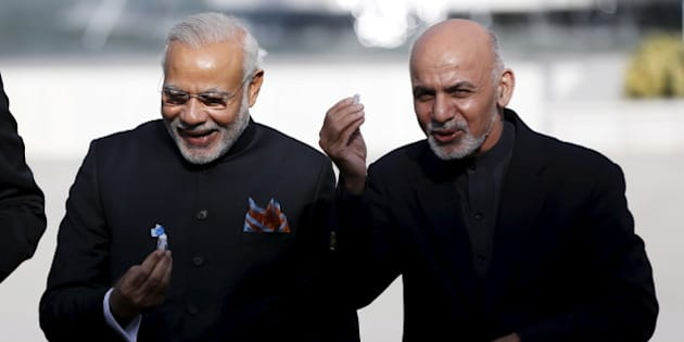 India's Prime Minister Narendra Modi (L) and Afghan president Ashraf Ghani hold sweets as they inaugurate Afghanistan's new parliament building, which was built with the Indian government's financial assistance, in Kabul, Afghanistan December 25, 2015. REUTERS/Omar Sobhani