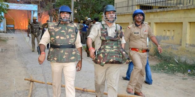 Indian police patrol during clashes with members of a sect said to have been living illegally at the Jawahar Bagh park in Mathura on June 2, 2016. Clashes between Indian police and followers of a revolutionary sect have left at least 23 people dead after an operation to evict thousands of people from parkland erupted into violence, officials said June 3. Two police officers were among those killed in the overnight clashes during a move to expel around 3,000 sect followers who had illegally occupied public land in the city of Mathura for the last two years.    / AFP / STR        (Photo credit should read STR/AFP/Getty Images)