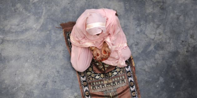 DADRI, INDIA - NOVEMBER 10: A Muslim woman pray in her home at Bisada village on November 10, 2015 in Dadri, India. Residents in Bisada village are not celebrating Diwali this year as they believe there is no charm in the village left after the lynching of Mohammad Akhlaq in the month of September. (Photo by Burhaan Kinu/Hindustan Times via Getty Images)