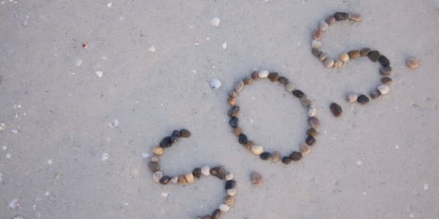 S.O.S written on the beach with stones