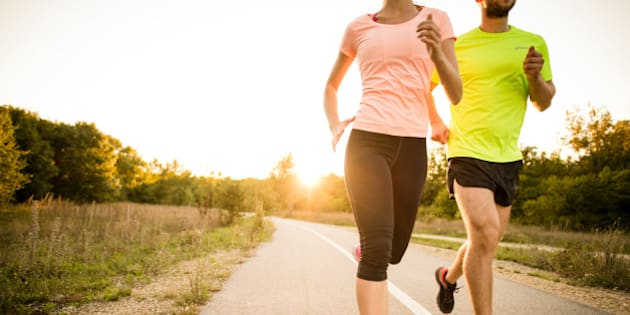 Detail of young people jogging together in nature with sun setting behind them.