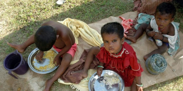 Homeless children eat food at a slum area on the outskirts of Agartala, capital of India's northeastern state of Tripura June 22, 2007. REUTERS/Jayanta Dey (INDIA)