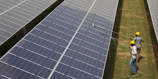 """Workers clean photovoltaic panels inside a solar power plant in Gujarat, India, in this July 2, 2015 file photo. The likely collapse of SunEdison Inc's solar project in India, the first of 32 planned """"ultra mega"""" complexes, could delay Prime Minister Narendra Modi's goal to increase renewable energy fivefold by several years and probably cost consumers more. REUTERS/Amit Dave/Files"""