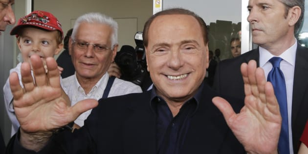 AC Milan president Silvio Berlusconi waves to supporters outside the Milanese soccer club's headquarters, in Milan, Italy, Friday, July 3, 2015. Berlusconi has demanded new coach Sinisa Mihajlovic lead the club back into the Champions League. (AP Photo/Luca Bruno)