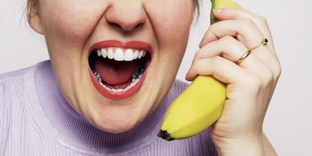 Woman holding banana and screaming, close up