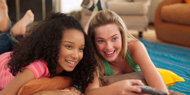 Two teenage girls lying down watching television with remote control smiling