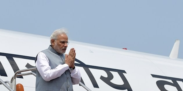 Indian Prime Minister, Narendra Modi gestures as he disembarks from the plane on his arrival at the Hazrat Shahjalal International Airport in Dhaka on June 6, 2015.  India's prime minister arrived in Bangladesh to seal a land pact which will finally allow tens of thousands of people living in border enclaves to choose their nationality after decades of stateless limbo.  AFP PHOTO/ Munir uz ZAMAN        (Photo credit should read MUNIR UZ ZAMAN/AFP/Getty Images)