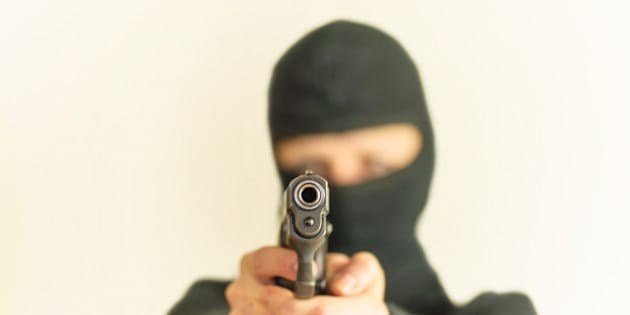 masked man points a gun