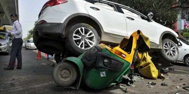 GURGAON, INDIA - JULY 15: People looking at the Hyundai SUV car which crashed into an auto-rickshaw after it was shot at by unidentified persons at MG Road on July 15, 2015 in Gurgaon, India. Unidentified persons in a black Santro fired at gangster Rakesh Yadav who was driving white Hyundai SUV, which jumped the road divider and fell on the auto-rickshaw, killing its driver. Yadav, who has over one dozen criminal cases registered against him, is the main accused in the killing of Hayatpur sarpanch (village head) Rakesh Kumar Yadav. (Photo by Parveen Kumar/Hindustan Times via Getty Images)