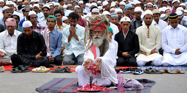 An Indian Hindu Sadhu performs an act of worship while Muslims offer Eid-ul-Fitr prayers at Jalori Gate in Jodhpur on August 9, 2013.  Muslims around the world are celebrating Eid al-Fitr, which marks the end of the fasting month of Ramadan AFP PHOTO/STR        (Photo credit should read STRDEL/AFP/Getty Images)