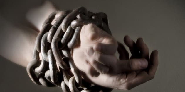 Close-up of wrists and hands bound in heavy metal chains