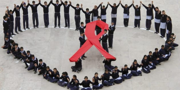 Students make a formation in the shape of a heart and a red ribbon during a HIV/AIDS awareness campaign on Valentine's Day in the northern Indian city of Chandigarh February 14, 2012. REUTERS/Ajay Verma (INDIA - Tags: TPX IMAGES OF THE DAY SOCIETY HEALTH)