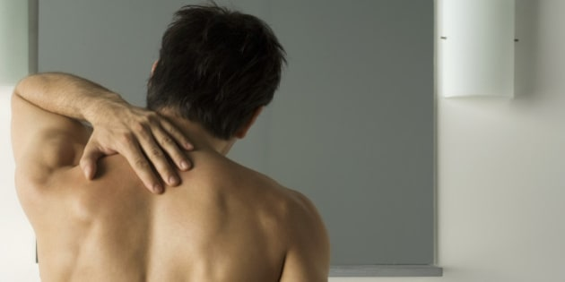 Bare-chested man touching his back, rear view
