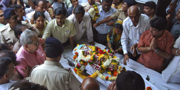 In this Tuesday, Aug. 20, 2013 photo, people pay last respects to anti-superstition activist Narendra Dabholkar who was killed in Pune, India. Police are searching for the two motorcycle-riding attackers, who in daylight gunned down the 67-year-old activist who crusaded against superstition, black magic and unholy Hindu godmen. (AP Photo/Nitin Lawate)