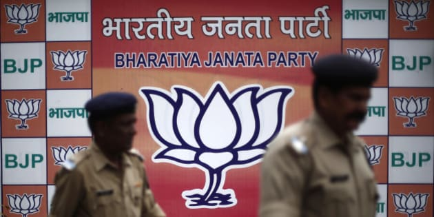 Security personnel walk past a hoarding of India's main opposition Bharatiya Janata Party (BJP) inside the party headquarters in New Delhi May 12, 2014. Indians voted on the last day of a mammoth election on Monday as challenger Modi sought a personal mandate in the holy city of Varanasi, crowning his campaign to rule the country with a mix of pro-business policies and Hindu nationalism.  REUTERS/Adnan Abidi (INDIA - Tags: POLITICS ELECTIONS)