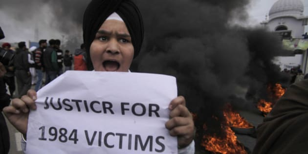 FILE - In this Sunday, Feb. 2, 2014 file photo, a young Sikh protester holds a placard as dozens of others burn tires during a protest against Congress party leader Rahul Gandhi for his recent remark on the country's 1984 anti-Sikh riots, in Jammu, India. India has blocked the release of a film on the assassination of former Indian Prime Minister Indira Gandhi, Rahul's grandmother, saying it glorifies her killers and could trigger violent protests, officials said Friday, Aug. 22, 2014. India's film certification board said the film glorified the two Sikh bodyguards who killed Gandhi to avenge her suppression of an insurgency that culminated in an army assault on the Golden Temple, Sikhism's holiest shrine. (AP Photo/Channi Anand, File)