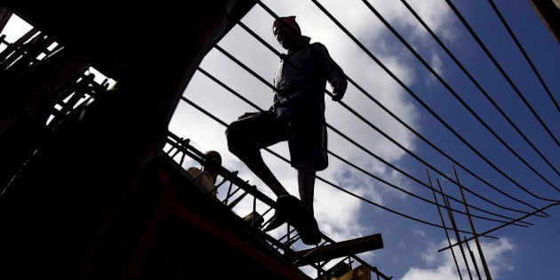 A labourer walks on an iron frame at the construction site of a residential complex on the outskirts of Kolkata, India, November 2, 2015. India's infrastructure output grew at its fastest pace in four months to 3.2 percent in September from a year ago, mainly driven by higher production of electricity and fertilisers, government data showed on Monday. REUTERS/Rupak De Chowdhuri
