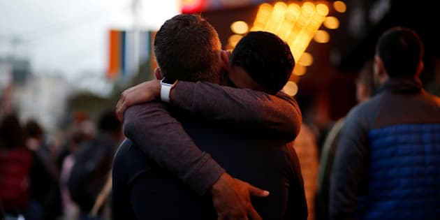 Ahmed Zaeem (R) embraces Billy Quimby, both of San Francisco, while attending a candlelight vigil for the victims of the Orlando attack against a gay night club, held in San Francisco, California, U.S. June 12, 2016. REUTERS/Beck Diefenbach     TPX IMAGES OF THE DAY