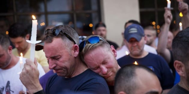 Paul Cox, right, leans on the shoulder of Brian Sullivan, as they observe a moment of silence during a vigil for a fatal shooting at an Orlando nightclub, Sunday, June 12, 2016, in Atlanta. (AP Photo/David Goldman)