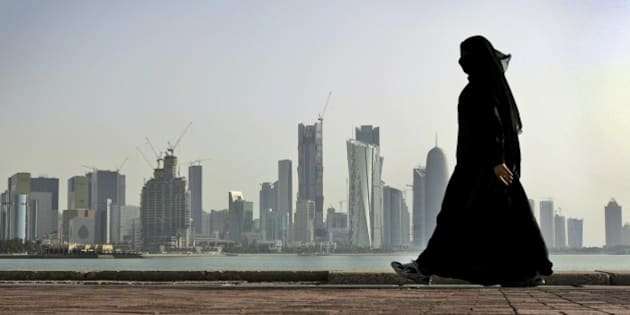 FILE- In this May 14, 2010 file photo, a Qatari woman walks in front of the city skyline in Doha, Qatar. A Dutch woman held in Qatar for nearly three months after telling police she had been raped was released Monday after receiving a 1-year suspended prison sentence, a Dutch diplomat said Monday. (AP Photo/Kamran Jebreili, File)