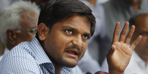 Hardik Patel, center, 22-year-old firebrand leader of Patidar Andolan Samiti addresses a press conference in New Delhi, India, Sunday, Aug. 30, 2015. Patel is leading an agitation for members of Gujarat state Patel community demanding government benefits for them under the Other Backward Class (OBC) quota. (AP Photo/Altaf Qadri)