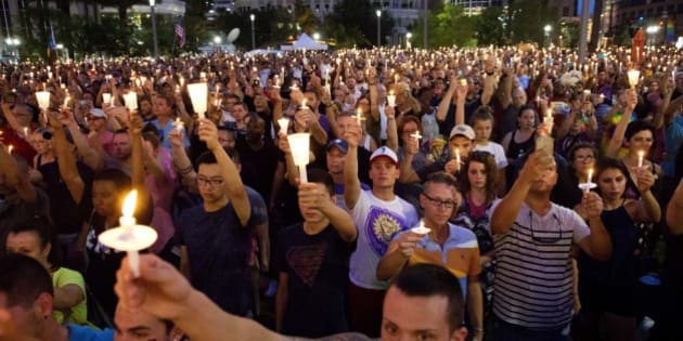 Crowd members hold up candles during a vigil downtown for the victims of a mass shooting at the Pulse nightclub Monday, June 13, 2016, in Orlando, Fla. (AP Photo/David Goldman)