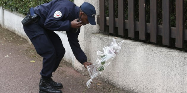 "A French police officer lays flowers while paying tribute to his colleagues killed in a knife attack near their home in Magnanville, west of Paris, France, Tuesday, June 14, 2016. French President Francois Hollande says that the stabbing attack that left two police officials dead was ""incontestably a terrorist act."" (AP Photo/Thibault Camus)"