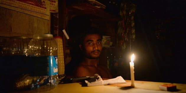 An Indian shopkeeper watches by candle-light during a power outage due to a fire which broke out at Kinari Bazar, a busy market in Chandni Chowk, the old quarters of New Delhi on August 25, 2014. Fire broke out in Kinari Bazaar in the narrow bylanes of Chandni Chowk with more than 25 fire tenders dispatched to put out the blaze.   AFP PHOTO/ Chandan KHANNA        (Photo credit should read Chandan Khanna/AFP/Getty Images)