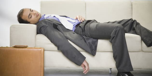 Indian businessman laying sleeping on sofa with briefcase