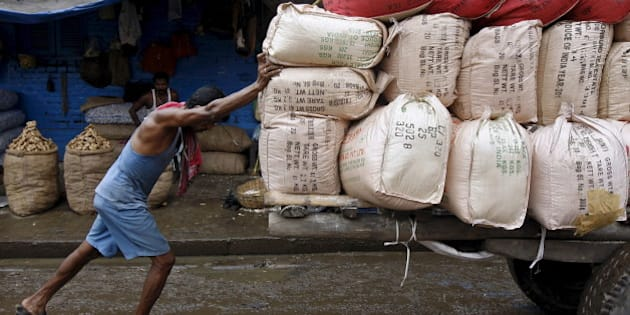 A labourer pushes a handcart loaded with sacks containing tea packets, towards a supply truck at a wholesale market in Kolkata, India, June 26, 2015. For years Indian businesses have lobbied for a nationwide sales tax, hoping to replace a chaotic structure that inflates costs and halts their trucks at state borders for duty payments, and to unify the country into one of the world's largest single markets. But after political compromises that finally got a goods and services tax (GST) bill before parliament, they have turned wary. Picture taken June 26.    REUTERS/Rupak De Chowdhuri