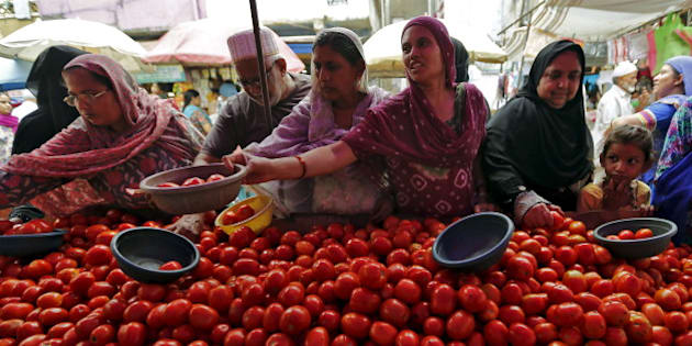 Local residents buy tomatoes from a roadside vegetable market in Ahmedabad, India, August 7, 2015. Entrenched expectations of high inflation in India are feeding into higher wages and other prices, which could tie India's central bank governor Raghuram Rajan's hands even as he faces growing pressure to cut interest rates for a fourth time this year to help a patchy economy. Picture taken August 7.  REUTERS/Amit Dave