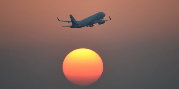 TOPSHOT - An airliner of India's IndiGo carrier flies over the setting sun in New Delhi on February 10, 2016. AFP PHOTO / Prakash SINGH / AFP / PRAKASH SINGH        (Photo credit should read PRAKASH SINGH/AFP/Getty Images)