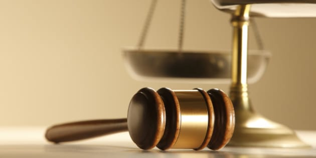 A gavel in front of a justice scale.