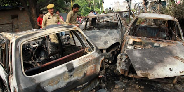 JAMMU, INDIA - JUNE 15: Jammu and Kashmir police men inspect the vehicles burnt by the protesters as city witnessed a near total bandh in protest against alleged desecration of a temple here last night on June 15, 2016 in Jammu, India. According to the news reports, mobile internet services were suspended in all 10 districts of Jammu region after the protests against the desecration of an ancient temple of Lord Shiva by youth of the other community whom was blamed for smashing the window panes and doors of a temple. (Photo by Nitin Kanotra/Hindustan Times via Getty Images)