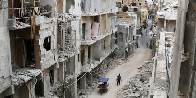Residents walk near damaged buildings in the rebel held area of Old Aleppo, Syria May 5, 2016. REUTERS/Abdalrhman Ismail/File Photo