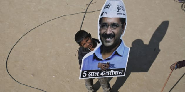A boy looks on as he holds a portrait of Arvind Kejriwal, chief of Aam Aadmi (Common Man) Party (AAP) and its chief ministerial candidate for Delhi, outside their party headquarters in New Delhi February 10, 2015. The upstart anti-establishment party crushed India's ruling Bharatiya Janata Party in an election for the Delhi assembly on Tuesday, smashing an aura of invincibility built around Prime Minister Narendra Modi since he swept to power last year. REUTERS/Anindito Mukherjee (INDIA - Tags: POLITICS ELECTIONS)