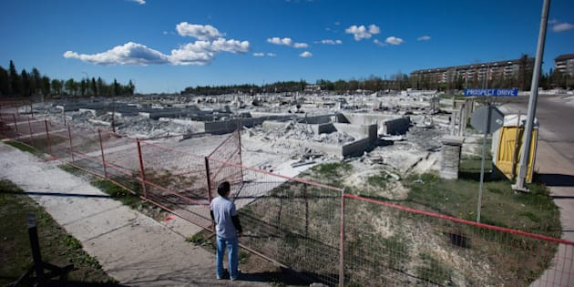 A resident surveys the damage of houses destroyed by wildfire in the Timberlea neighborhood of Fort McMurray, Alberta, Canada, on Sunday, June 5, 2016. Residents began returning home Wednesday and companies are resuming operations after Alberta wildfires forced the evacuation of more than 80,000 people from Fort McMurray and knocked more than 1 million barrels of production a day offline this month. Photographer: Darryl Dyck/Bloomberg via Getty Images