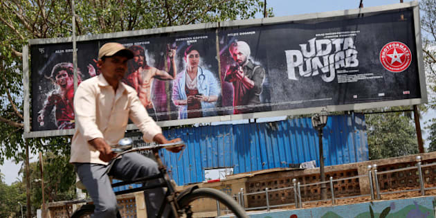 """A man rides his bicycle past a poster of the movie """"Udta Punjab"""" in Mumbai, India, June 13, 2016. REUTERS/Shailesh Andrade"""