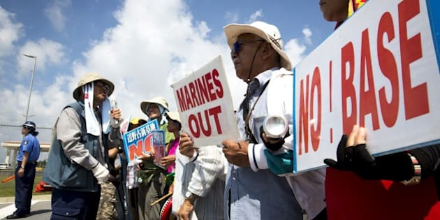 OKINAWA, JAPAN - JUNE 17:  People stage a rally against past incident of rape of a Japanese woman and drunk driving in Okinawa over American military presence in Japan in front of the US base in Camp Schwab, on June 17, 2016 in Nago, Okinawa, Japan. (Photo by Richard Atrero de Guzman/Anadolu Agency/Getty Images)