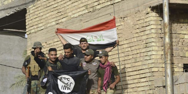 Iraqi security forces raise an Iraqi flag as they hold a flag of the Islamic State group they captured in central Fallujah, Iraq, after fighting against the Islamic State militants,  Friday, June 17, 2016. Iraqi special forces entered the center of Fallujah city early Friday, taking over a government complex and a neighborhood that served as a base for the Islamic State group militants after intense fighting. (AP Photo)